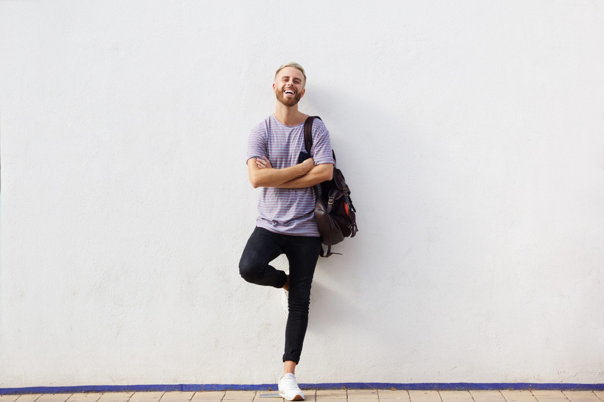 Full body happy young man with beard leaning against wall with arms crossed